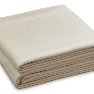 An undyed merino wool blanket, folded neatly against a white background.